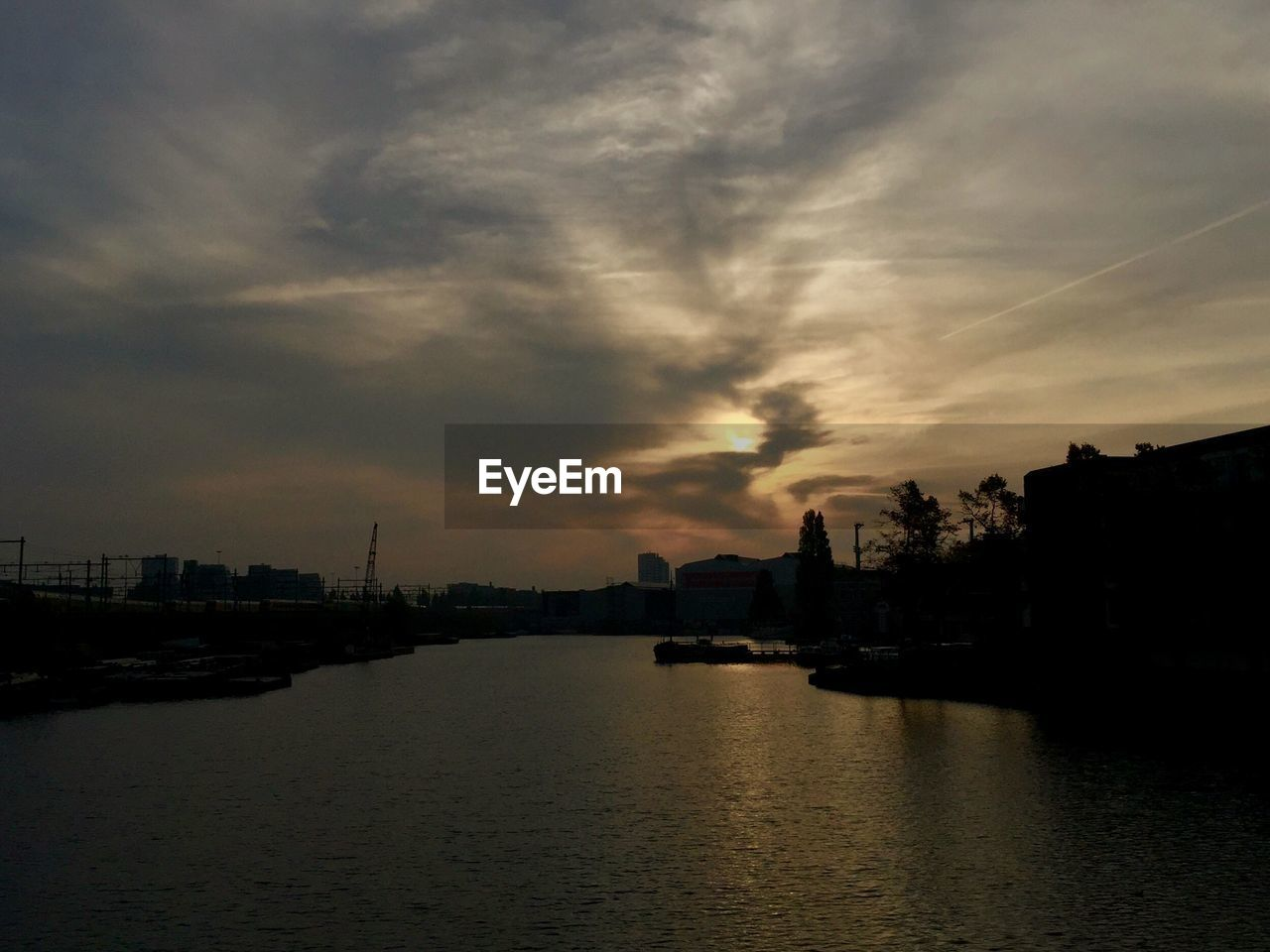 Scenic view of river amidst silhouette buildings against sky during sunset