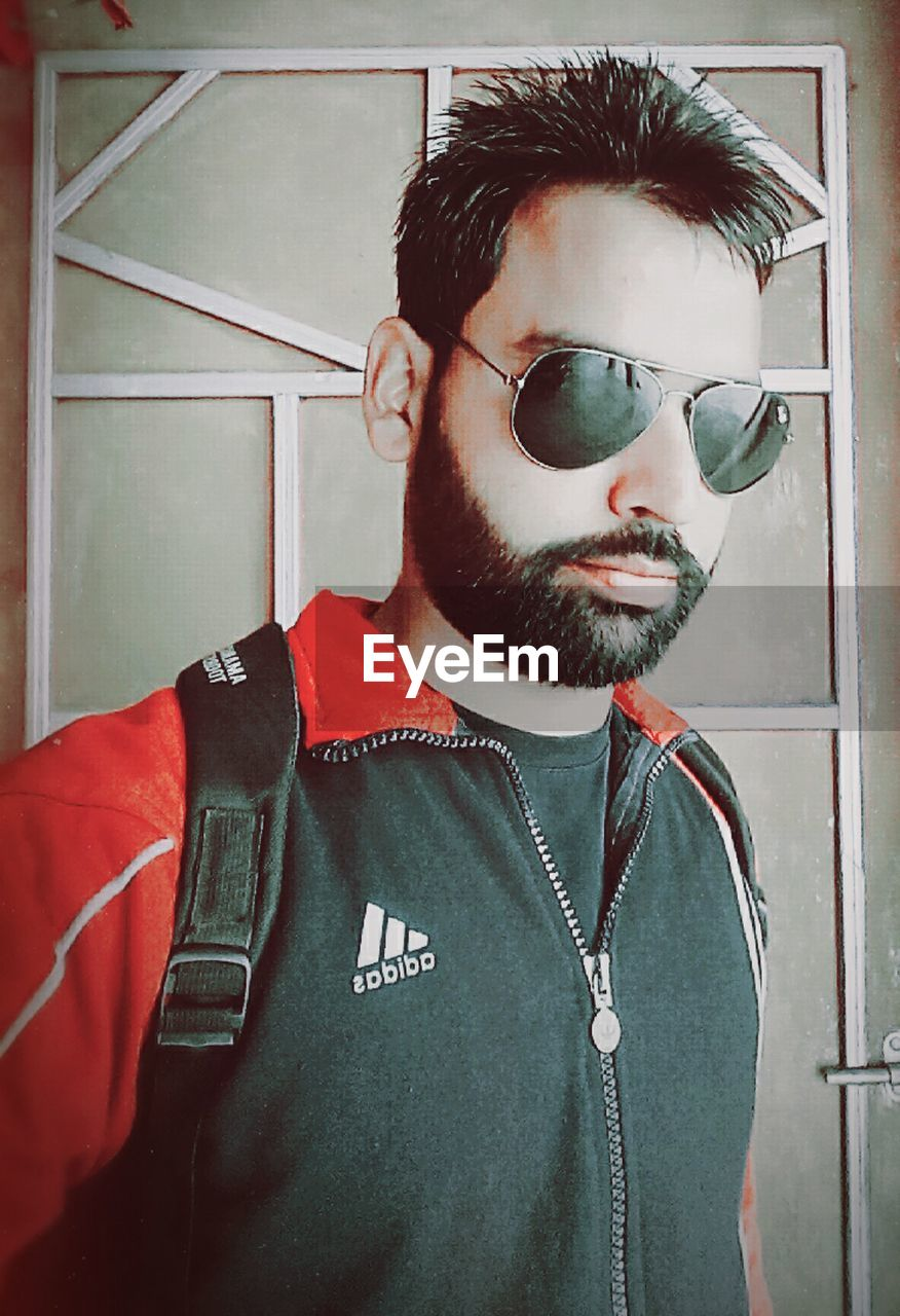 young adult, young men, beard, real people, one person, sunglasses, front view, lifestyles, leisure activity, indoors, home interior, standing, day, one young man only, portrait, people