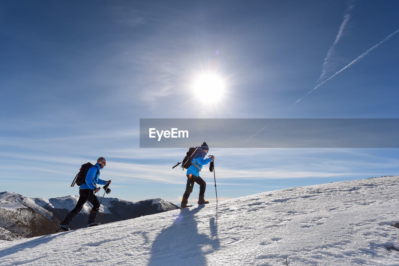 sky, sunlight, mountain, leisure activity, winter, snow, nature, cold temperature, beauty in nature, sport, winter sport, day, full length, scenics - nature, lifestyles, sun, real people, lens flare, adventure, mountain range, outdoors, snowcapped mountain