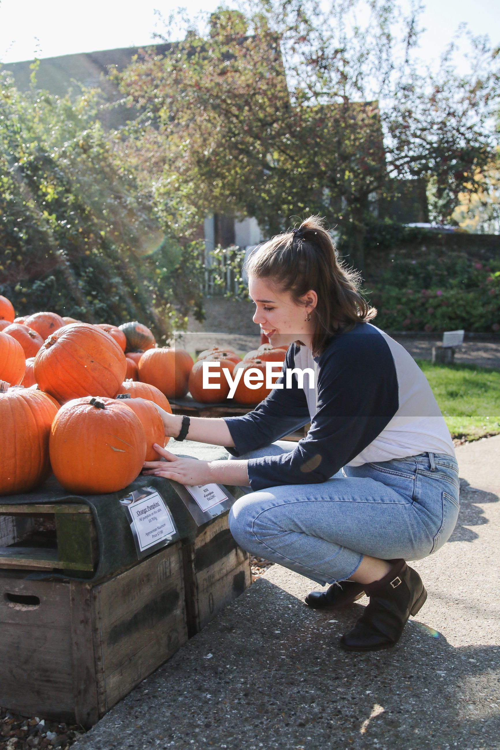 Side view full length of young woman holding pumpkin
