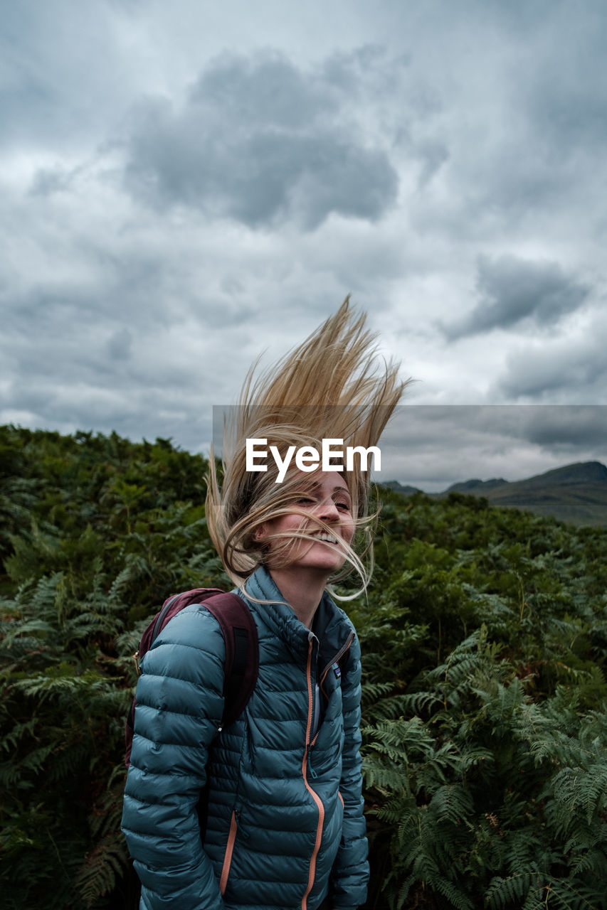 Blonde woman whipping hair in front of field of ferns