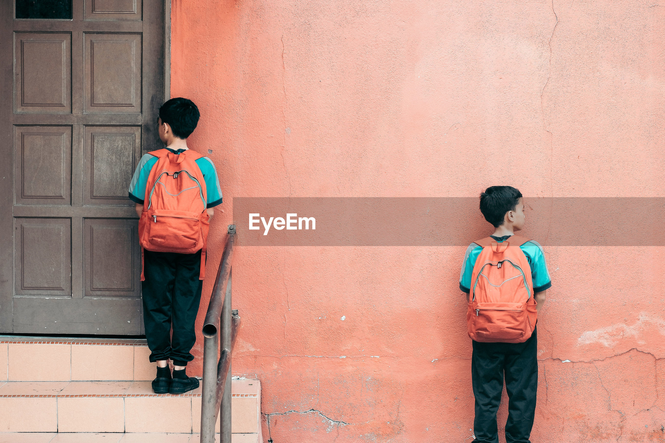 Rear view of boys with backpacks standing outside school