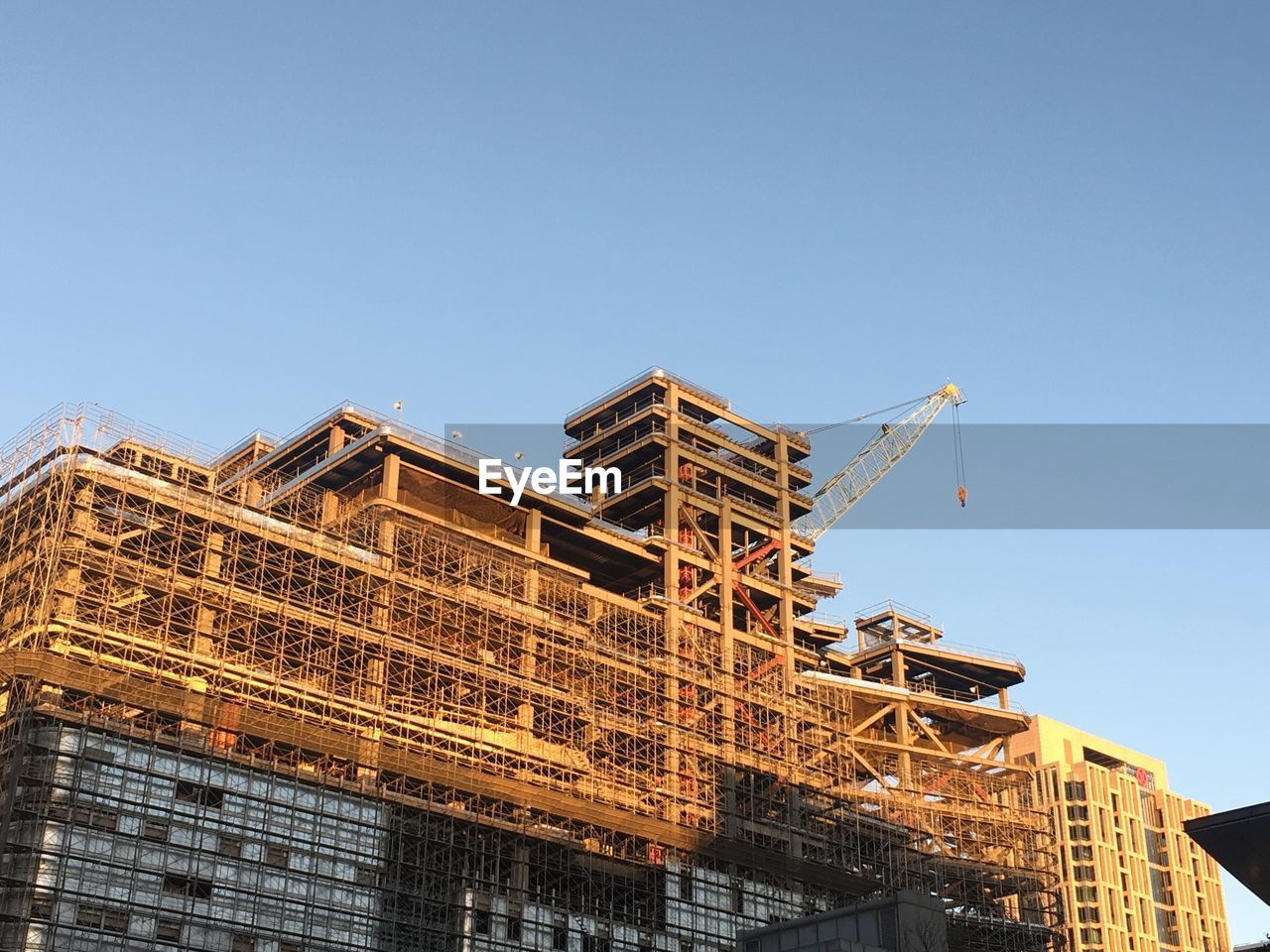 Low Angle View Of Under Construction Building Against Clear Blue Sky
