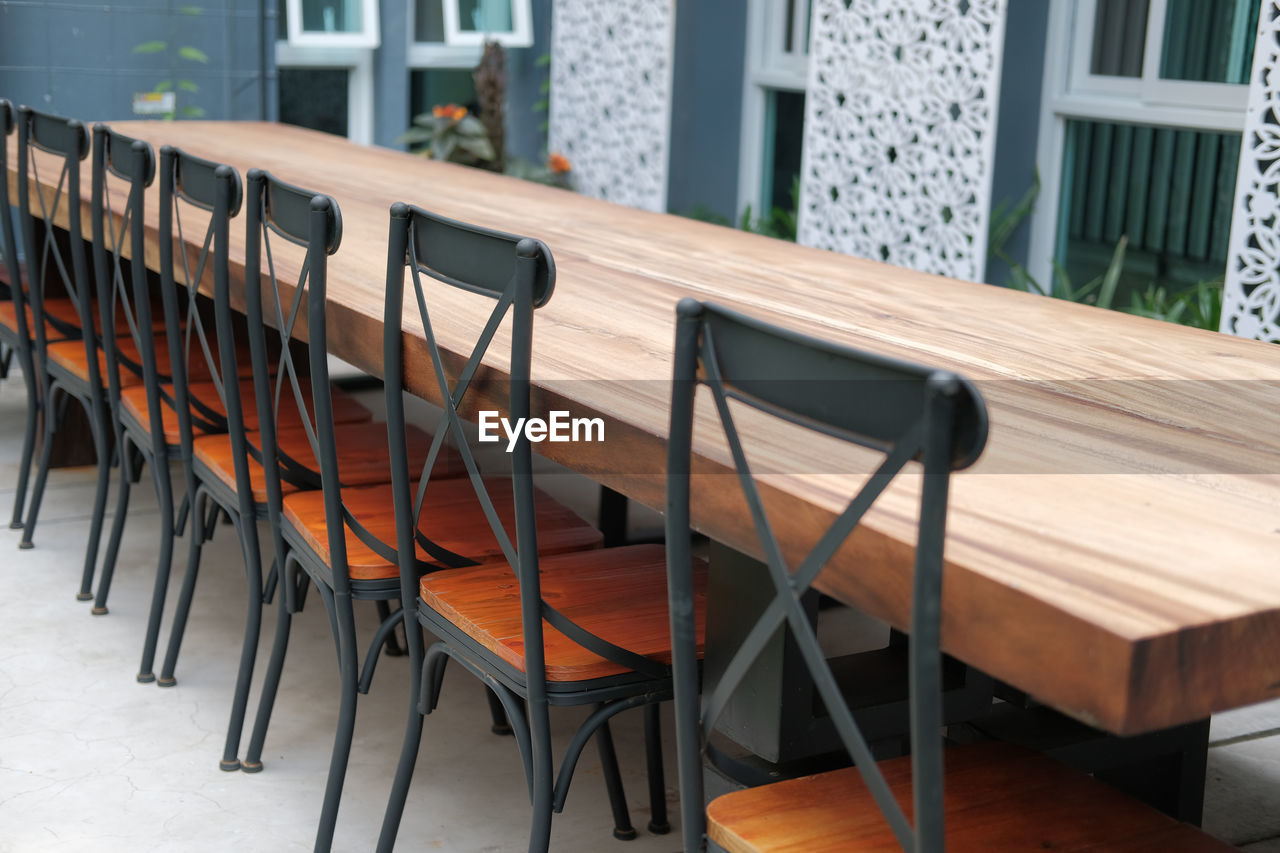 EMPTY CHAIRS AND TABLE IN RESTAURANT AGAINST BUILDING