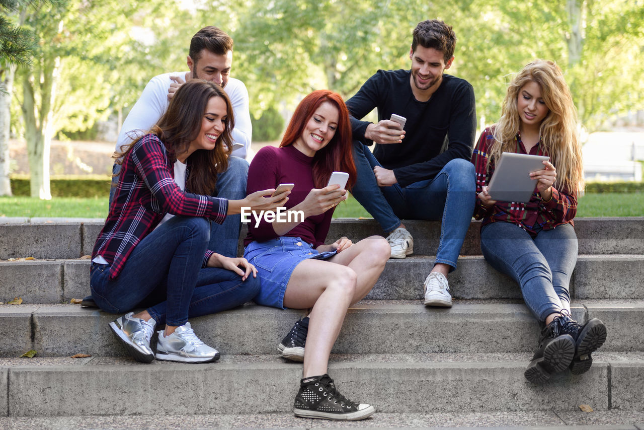 Friends using wireless technology while sitting on staircase