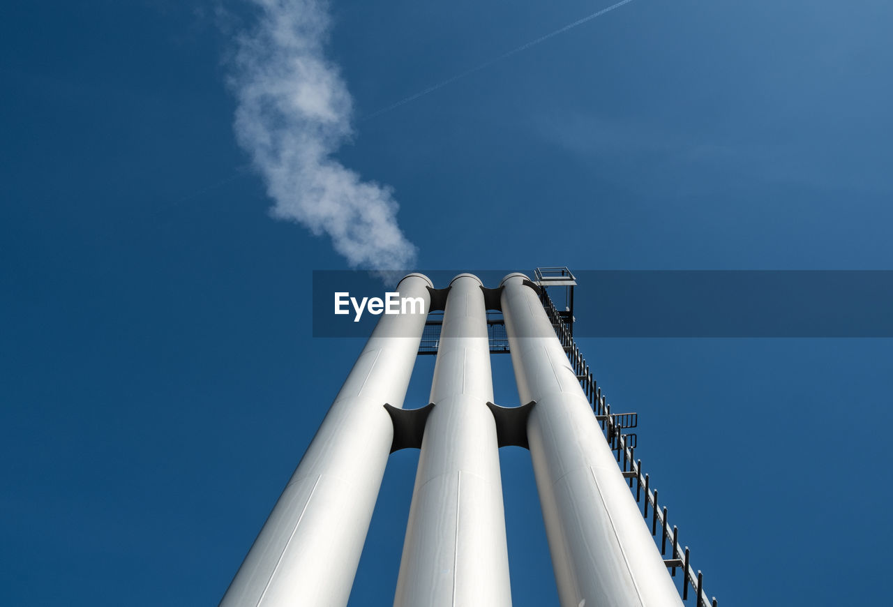 Low Angle View Of Chimneys Against Blue Sky