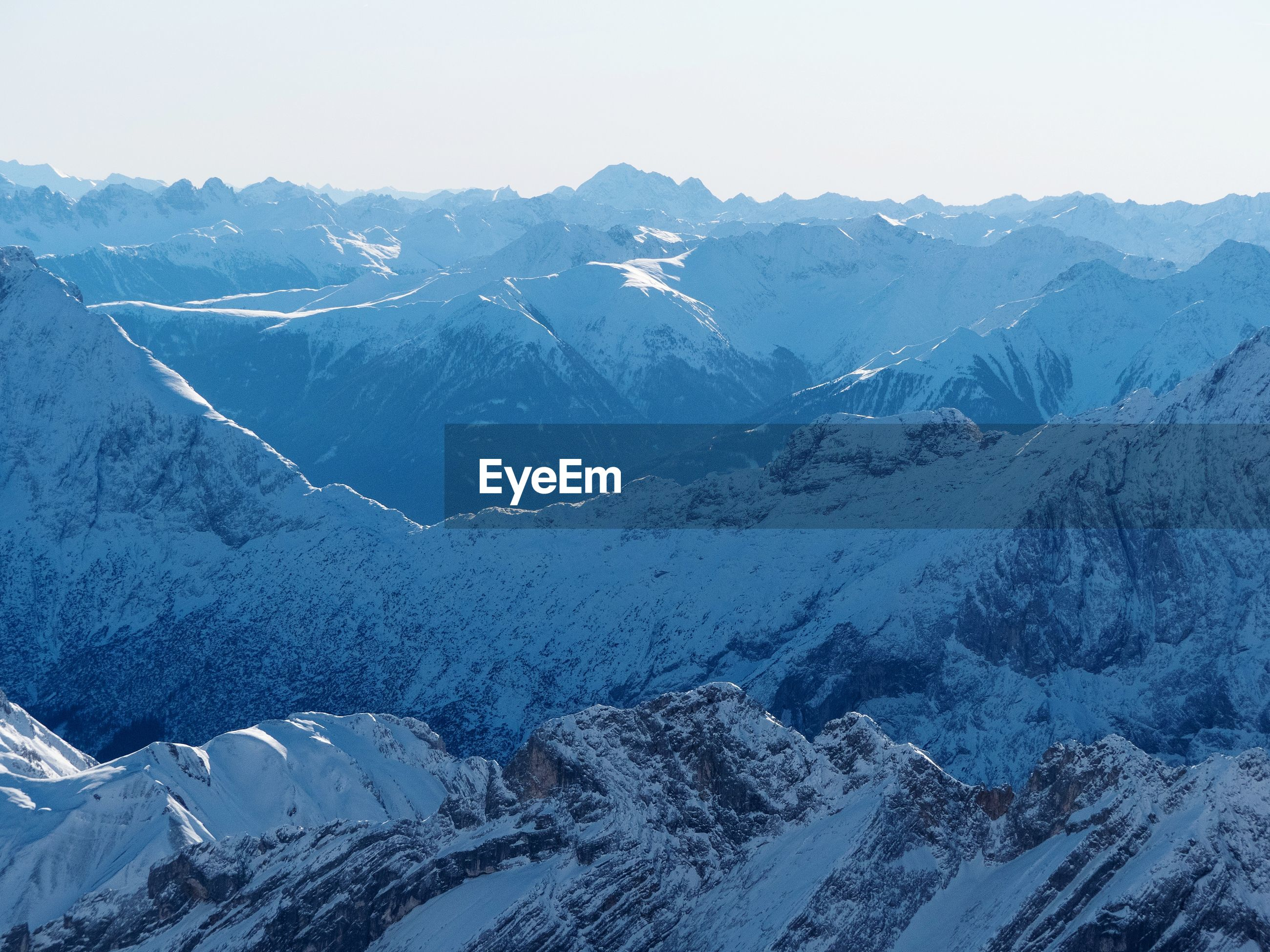Aerial view of snowcapped mountains against clear sky