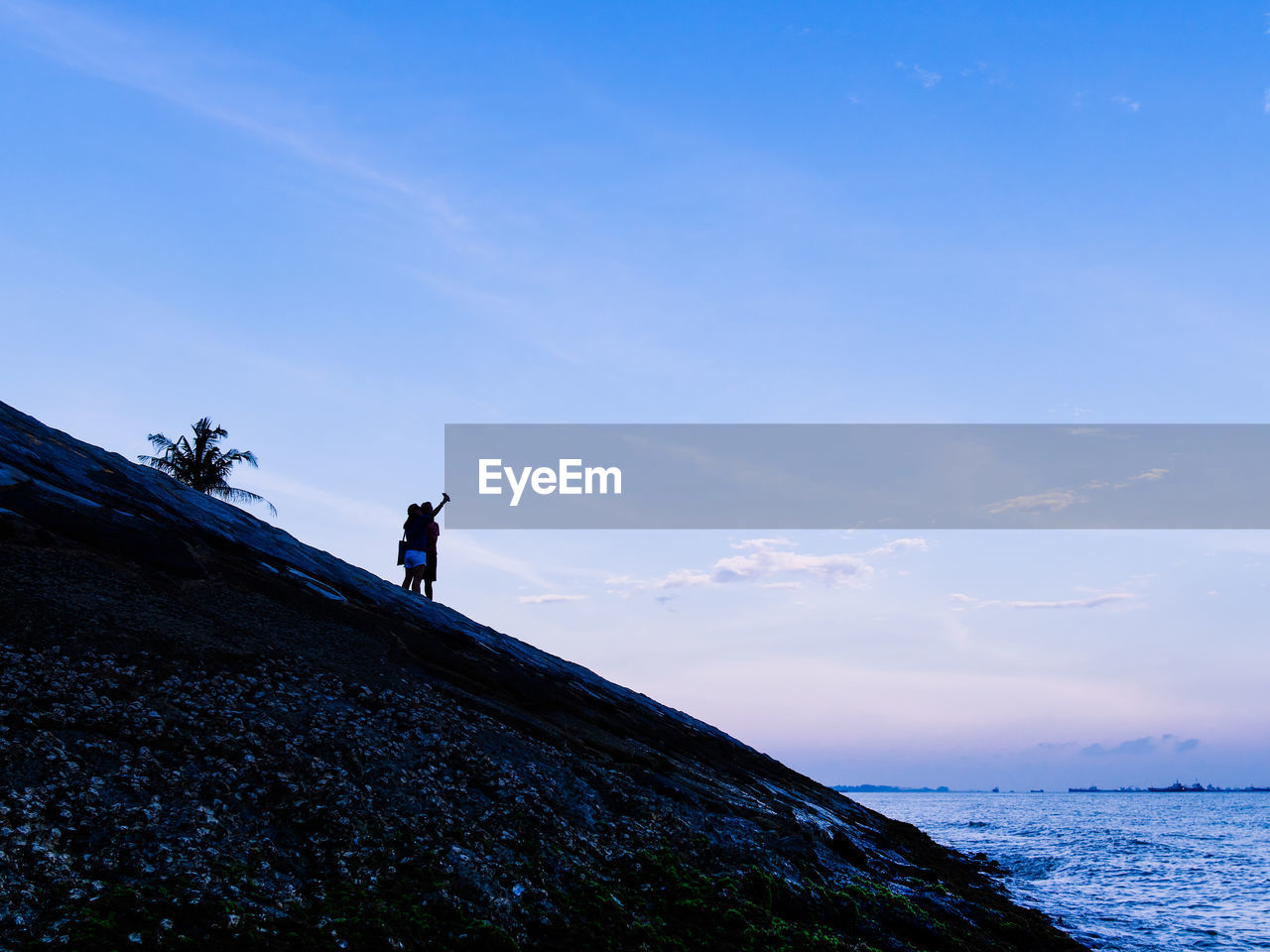 sky, leisure activity, beauty in nature, real people, scenics - nature, lifestyles, water, sea, rock, nature, rock - object, men, solid, land, tranquil scene, one person, standing, blue, tranquility, outdoors