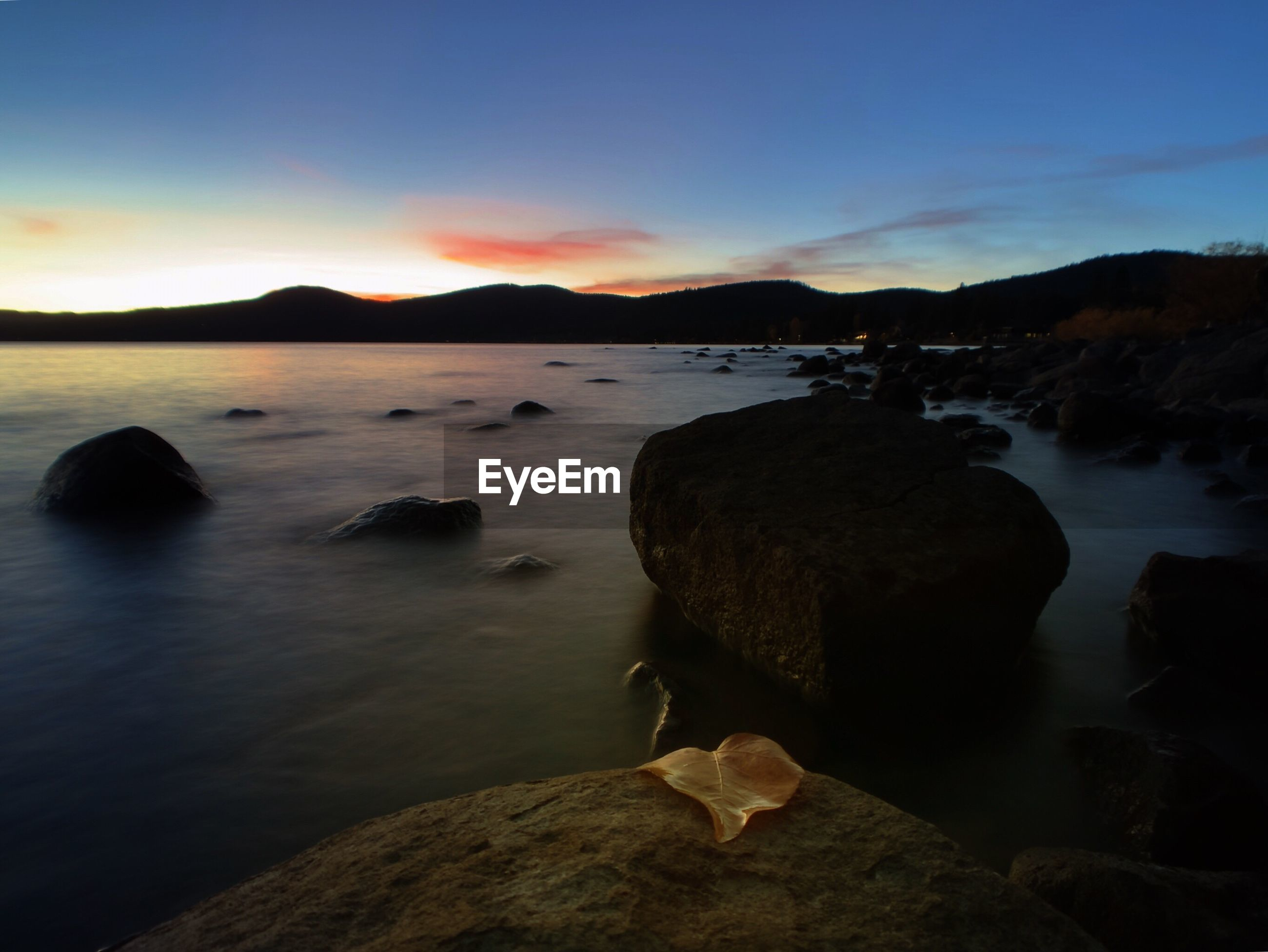SCENIC VIEW OF ROCKS ON BEACH AGAINST SKY DURING SUNSET