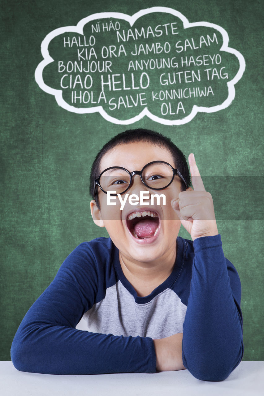 Portrait of boy gesturing on speech bubble against green board
