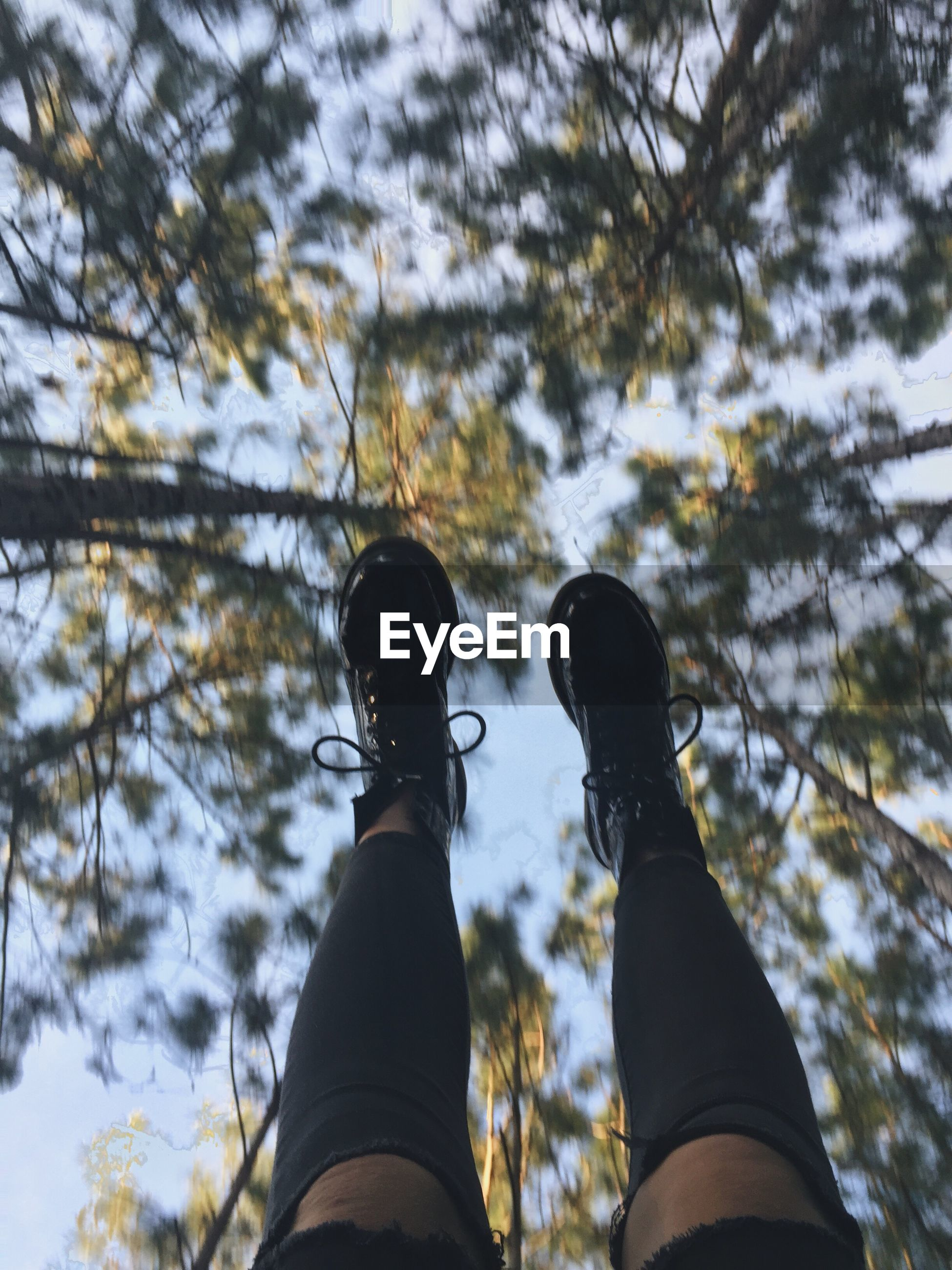 Low angle view of human feet against clear sky