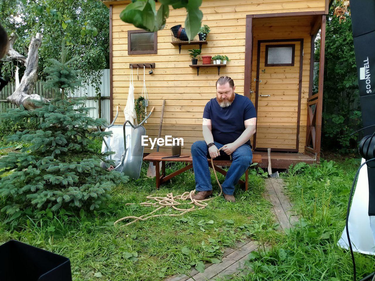MAN SITTING IN YARD