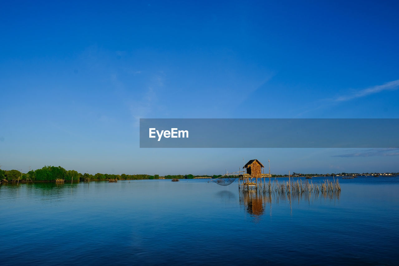BICYCLE ON LAKE AGAINST BLUE SKY