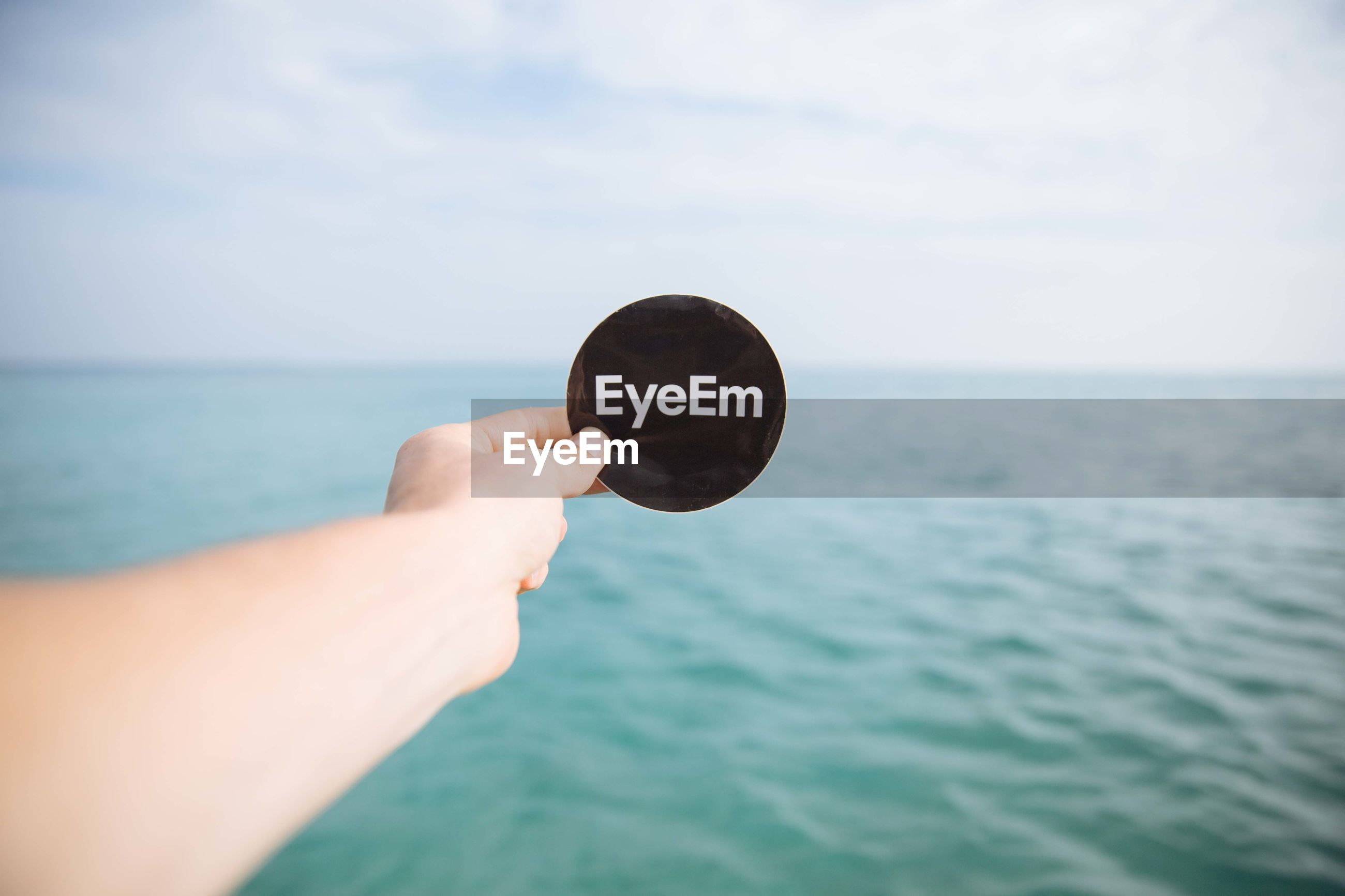 Cropped image of hand holding eyeem label against sea