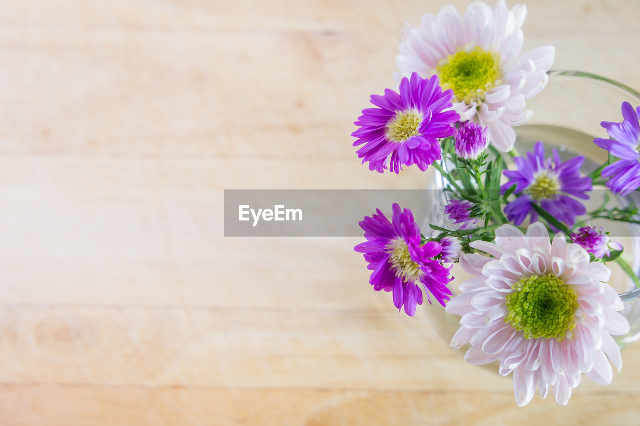 flowering plant, flower, freshness, vulnerability, fragility, plant, petal, beauty in nature, flower head, inflorescence, close-up, table, pink color, nature, no people, wood - material, high angle view, indoors, growth, focus on foreground, purple, pollen, flower arrangement