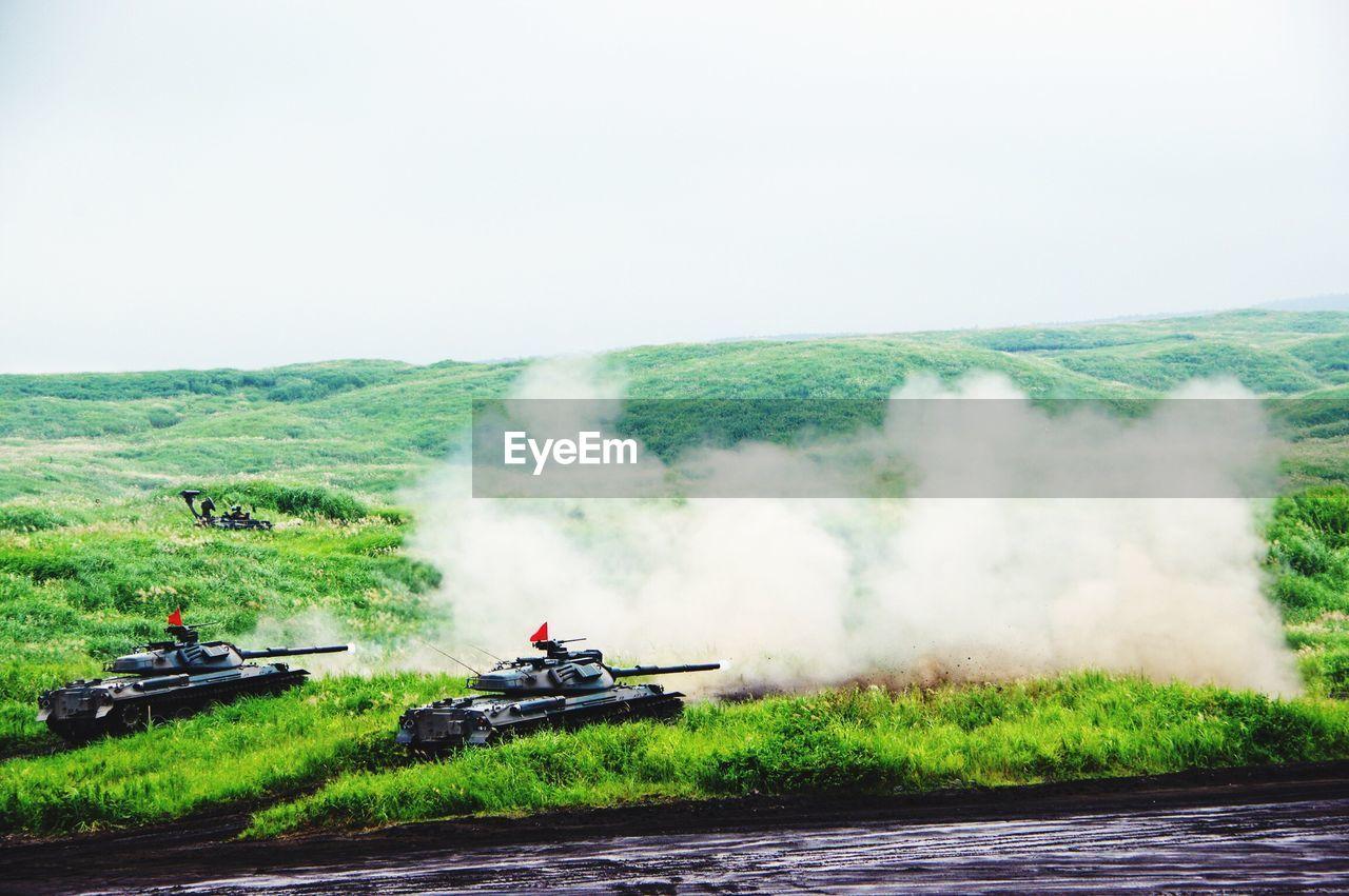 Armored Tanks Firing On Grassy Field Against Sky