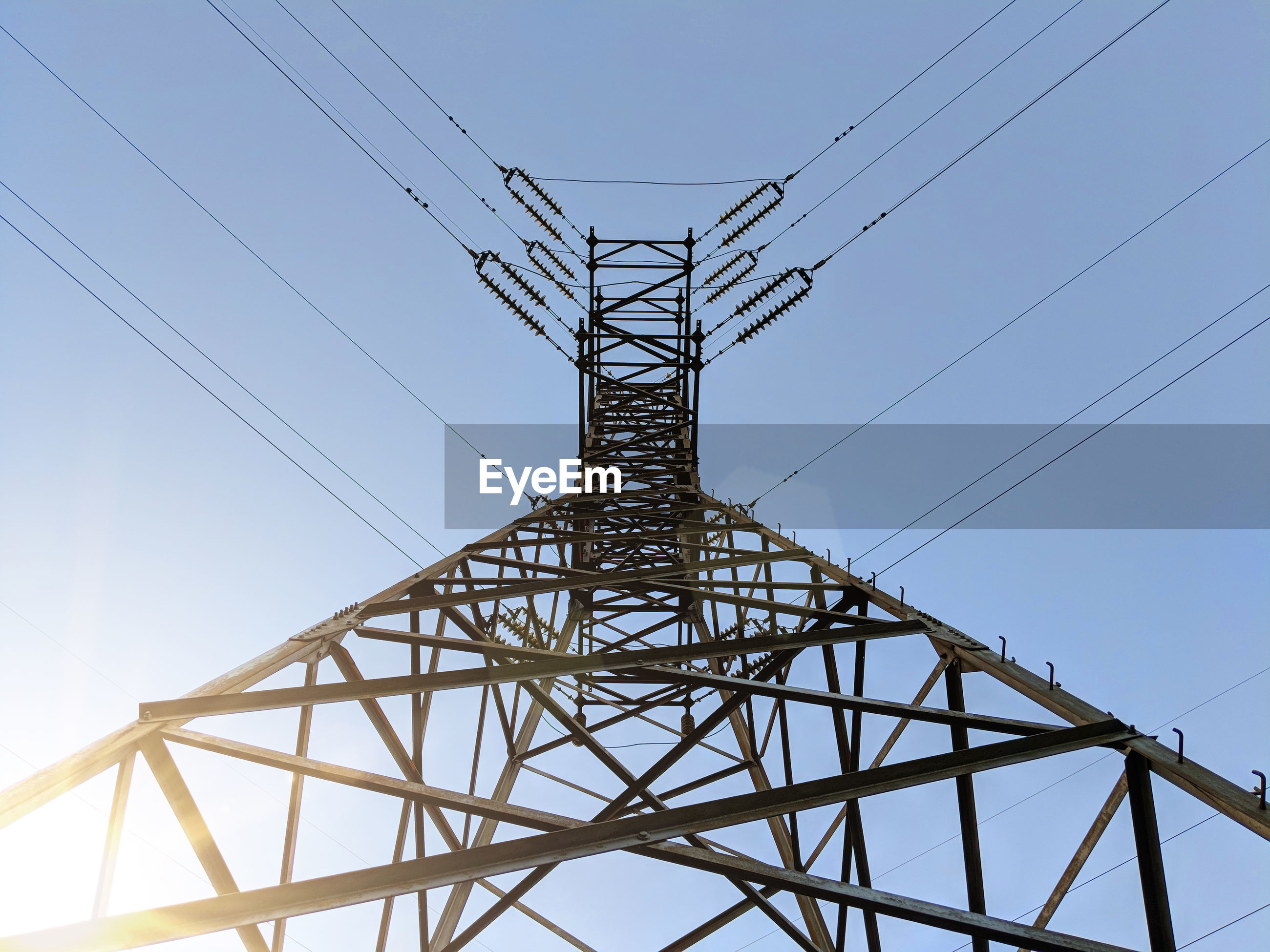 Low angle view of electricity pylon against clear sky during sunny day
