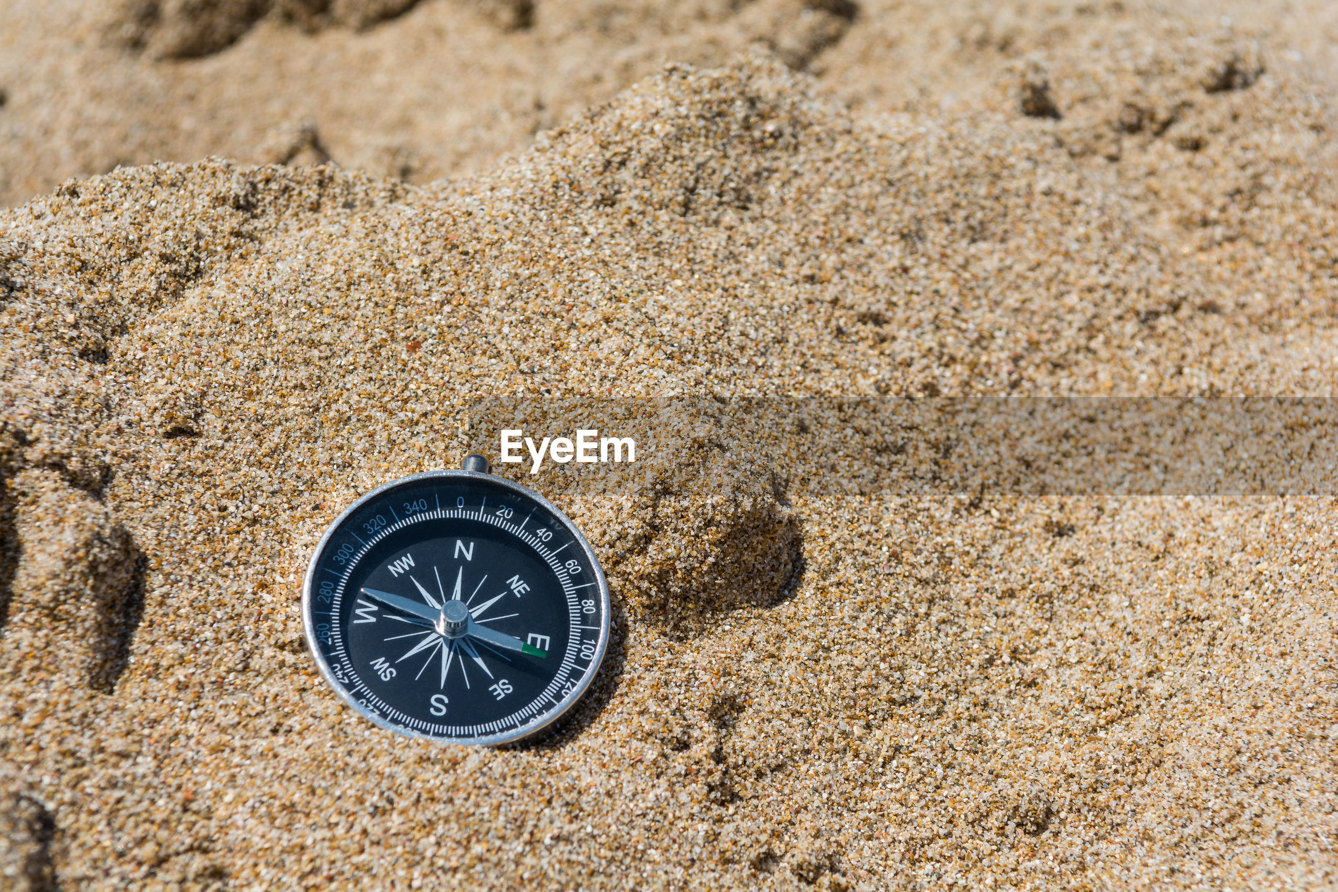 High angle view of navigational compass on sand