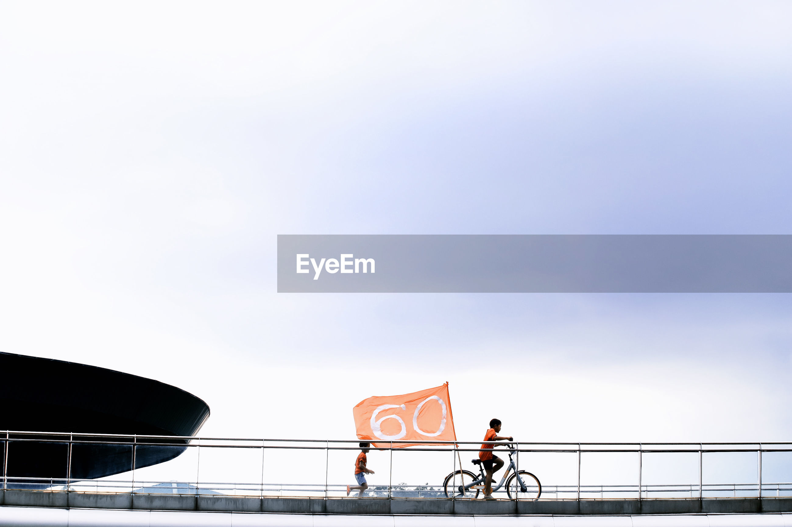 Boys with bicycle on footbridge by railing and flag against sky