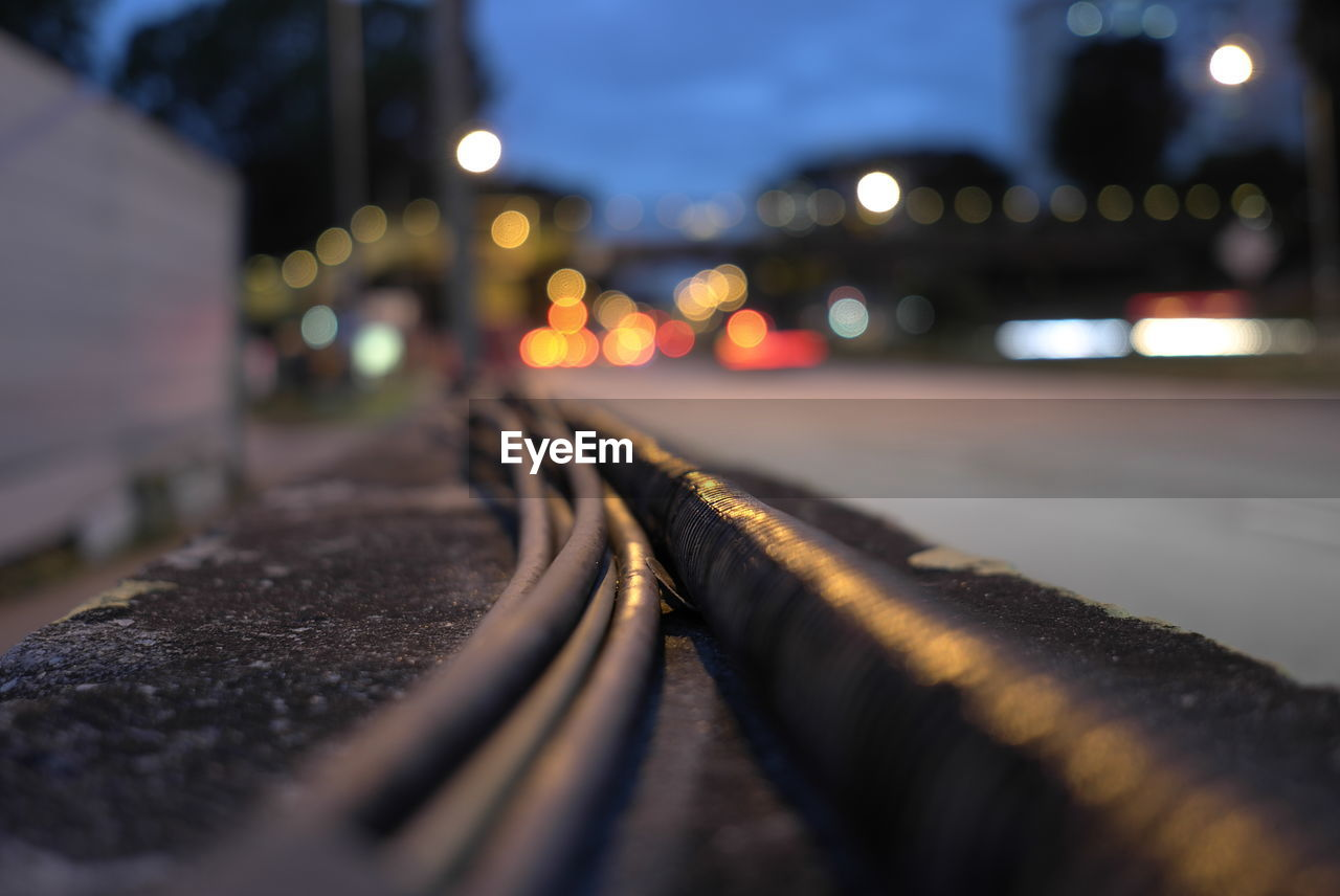 selective focus, illuminated, close-up, no people, night, architecture, metal, connection, street, city, outdoors, built structure, railing, transportation, glowing, nature, in a row, track, surface level, cable