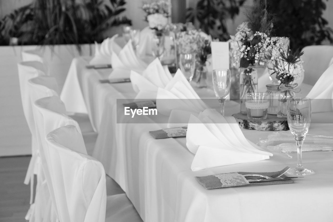 table, wedding, celebration, event, no people, glass, household equipment, drinking glass, indoors, place setting, setting, glass - material, focus on foreground, chair, decoration, arrangement, seat, furniture, ceremony, napkin, wedding ceremony