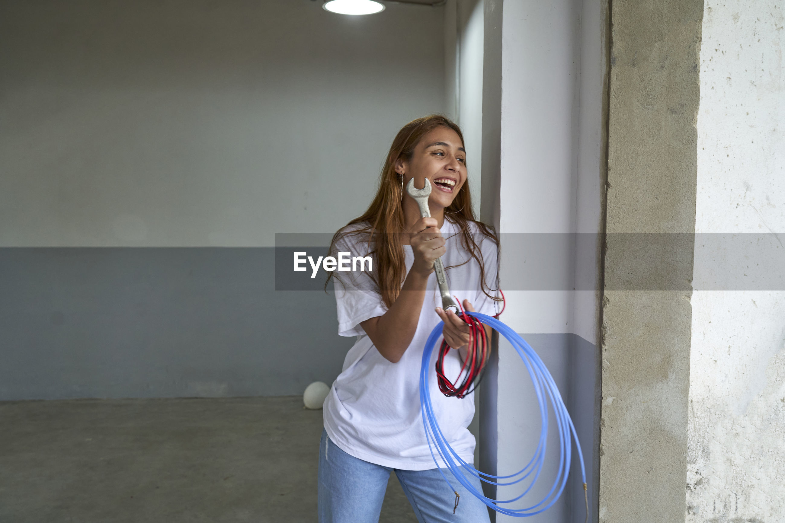 YOUNG WOMAN SMILING AGAINST WALL