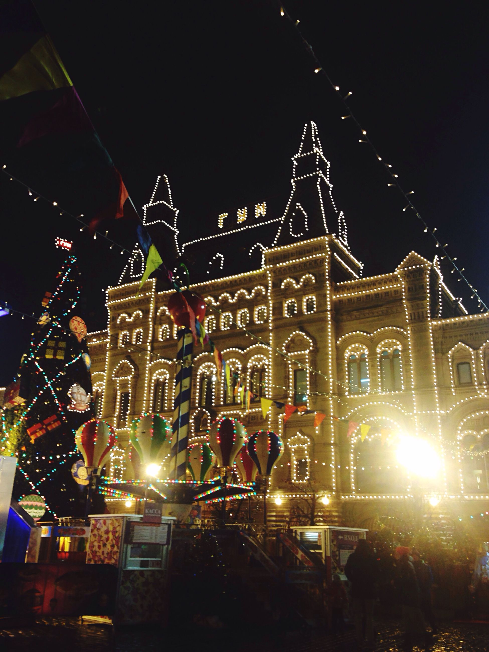 night, illuminated, large group of people, built structure, architecture, building exterior, outdoors, real people, celebration, arts culture and entertainment, amusement park, christmas lights, men, place of worship, crowd, sky, women, clear sky, city, people