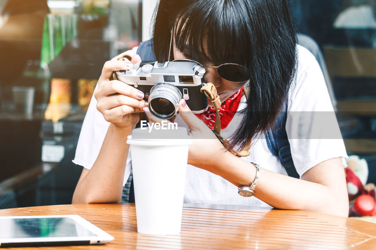Woman photographing disposable cup at table