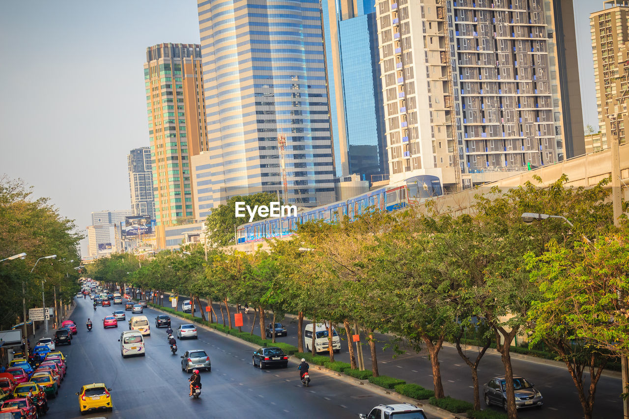 city, architecture, building exterior, car, built structure, motor vehicle, transportation, mode of transportation, street, land vehicle, building, tree, road, plant, city life, office building exterior, city street, sign, day, incidental people, skyscraper, modern, outdoors