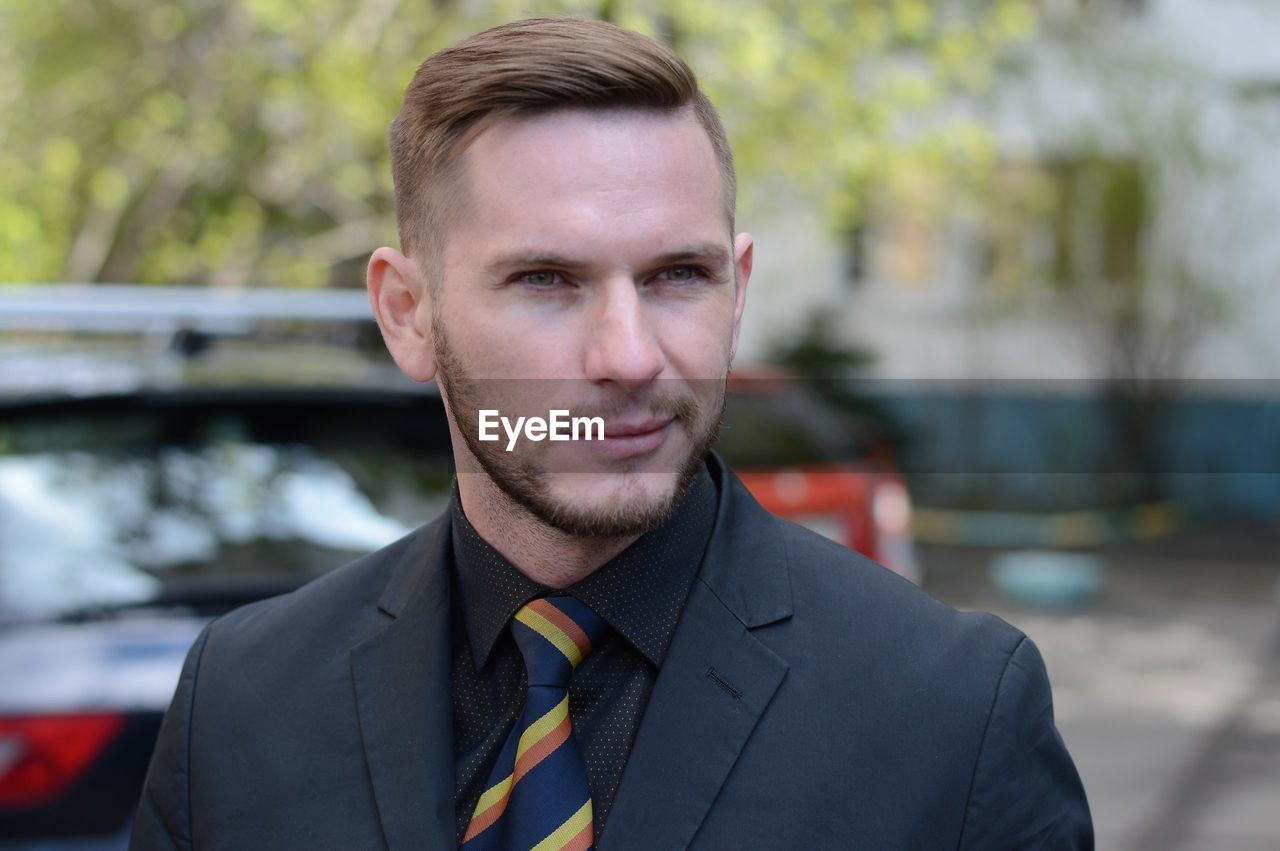 Close-up of handsome businessman looking away