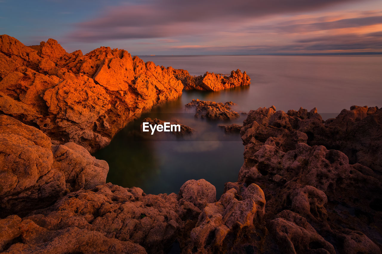 High Angle View Of Rocky Coastal Feature Against Sky