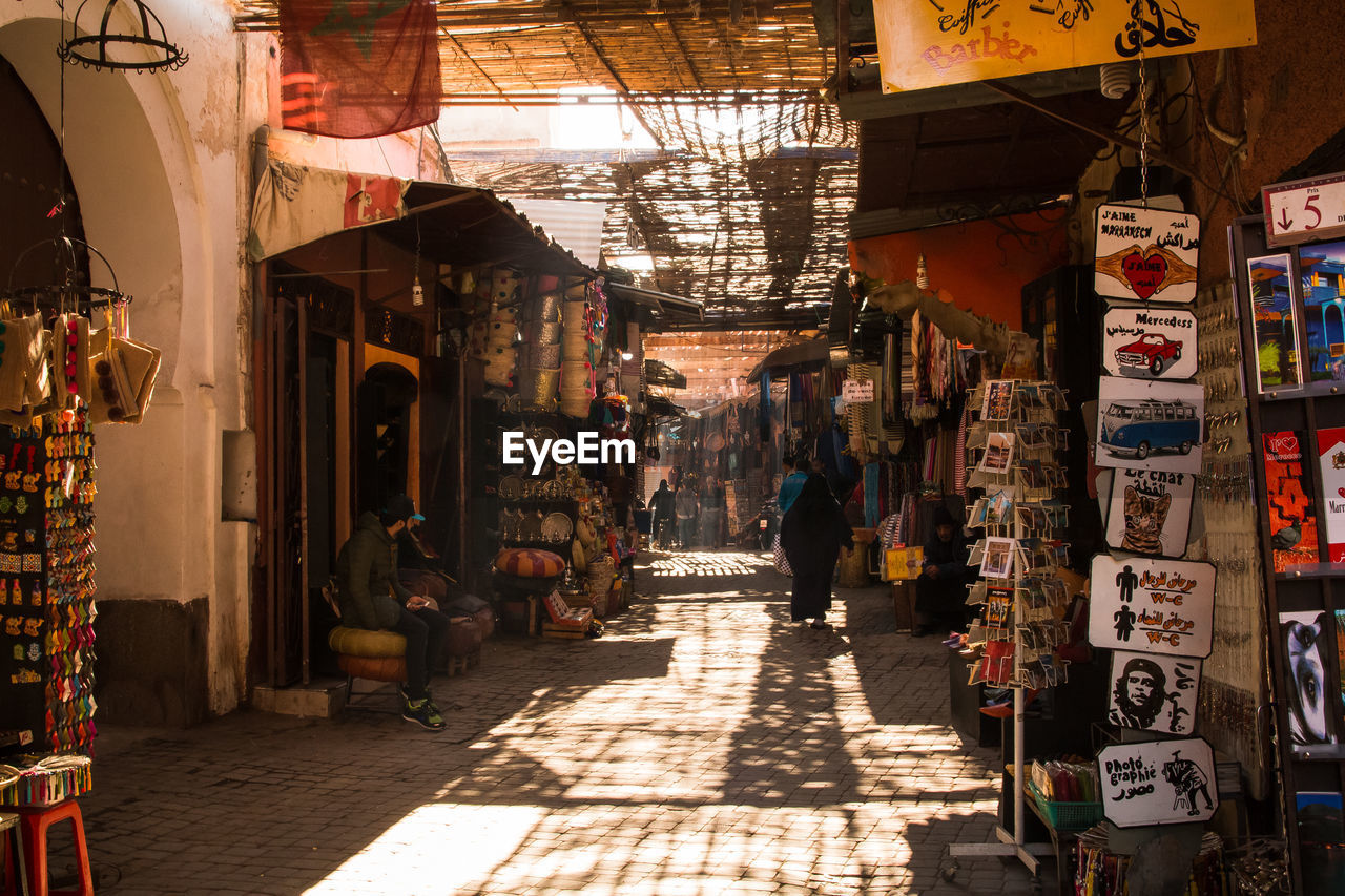 retail, market, store, sunlight, the way forward, day, built structure, architecture, incidental people, direction, shadow, market stall, text, large group of objects, for sale, shopping, small business, lighting equipment, business, illuminated, retail display