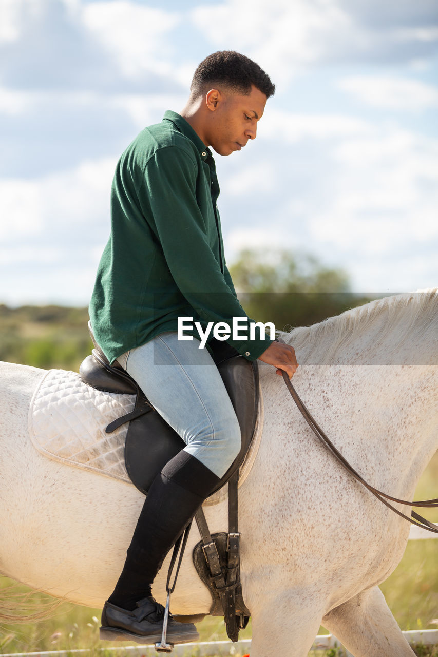 Full length of young man riding horse against tree