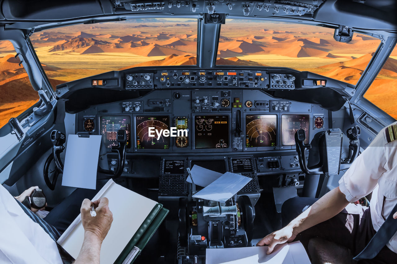 Midsection of pilots holding paper in cockpit over desert