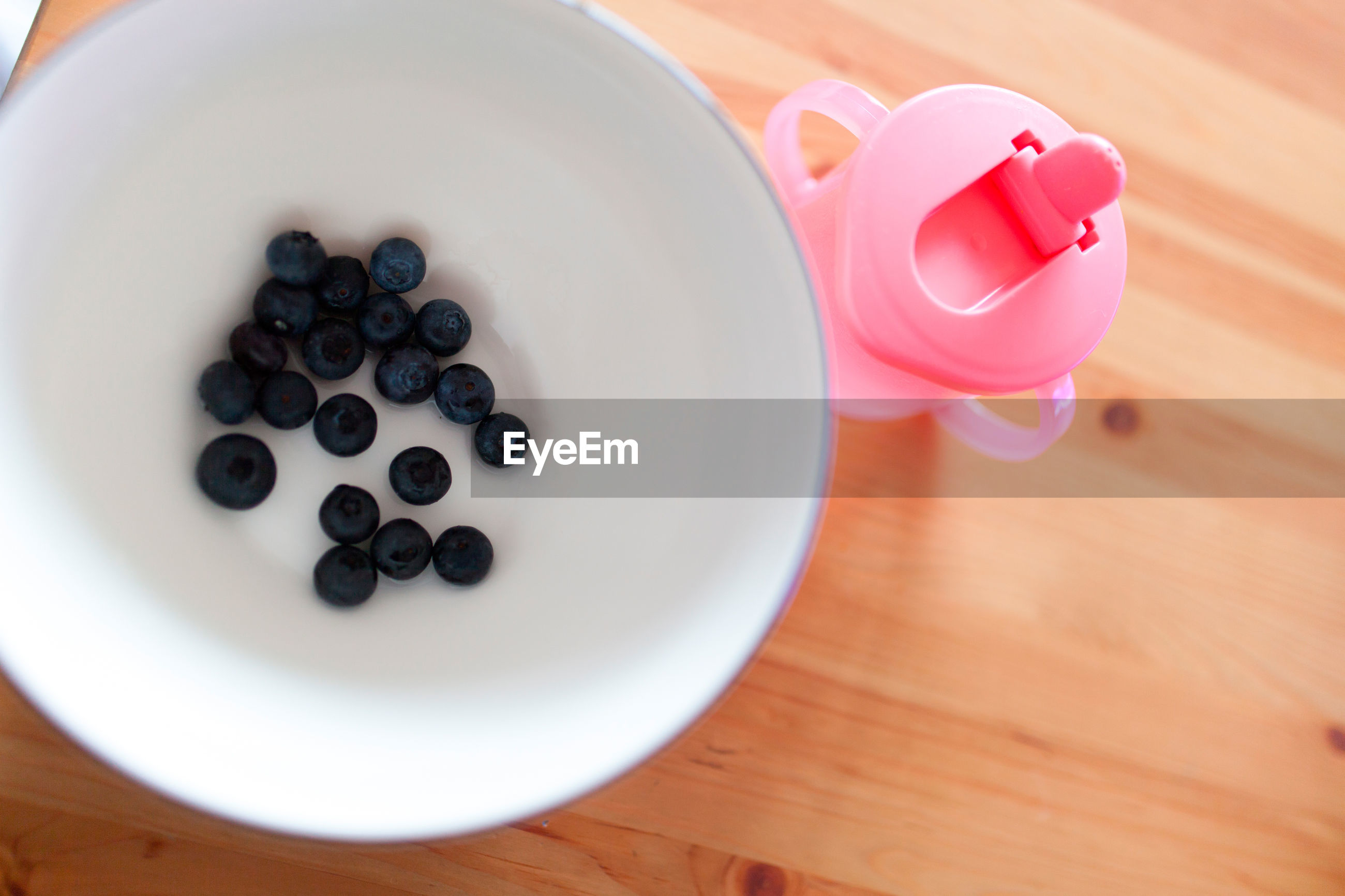 High angle view of blueberries in plate by pink bottle on table