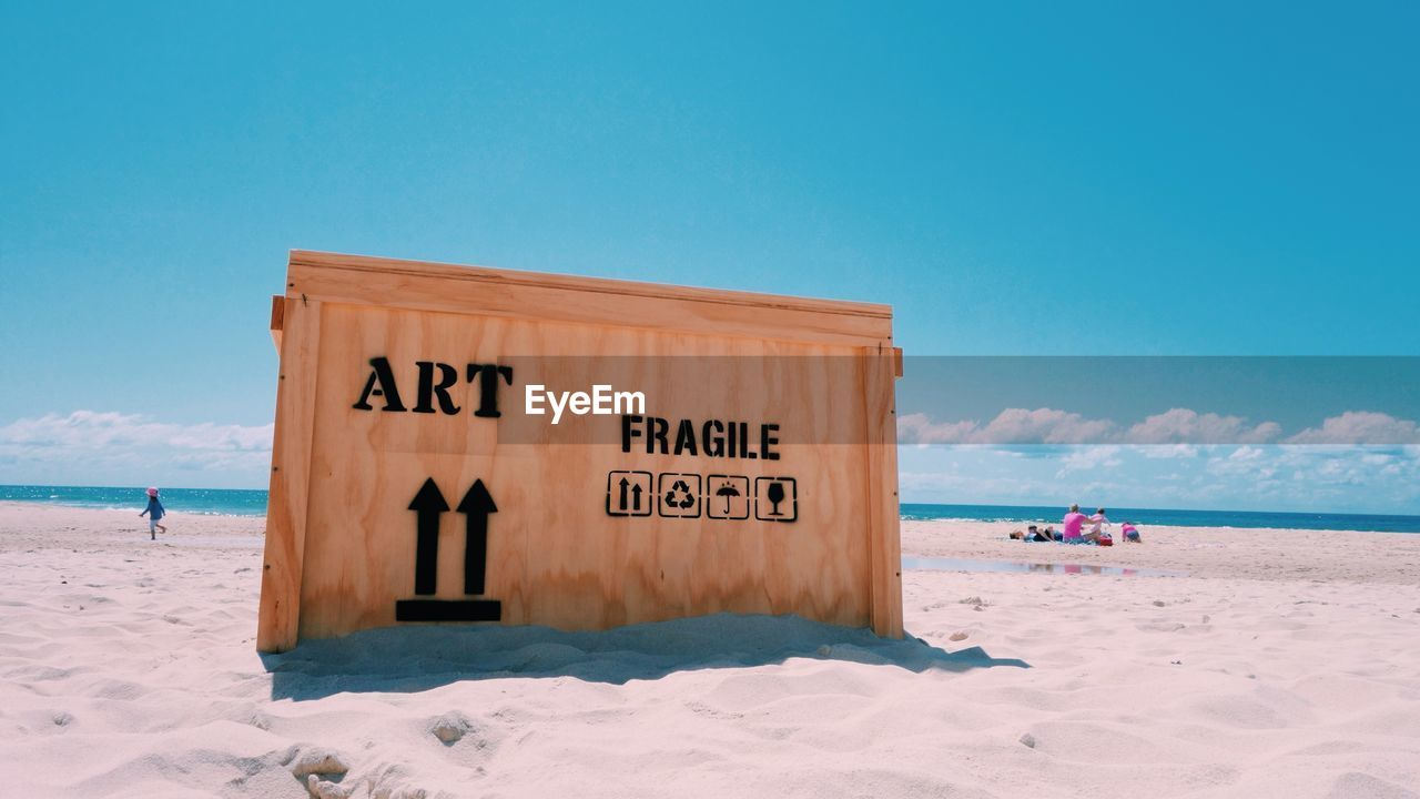 Wooden Box With Text At Sandy Beach On Sunny Day