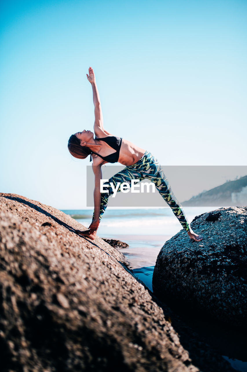 full length, lifestyles, real people, exercising, one person, balance, clear sky, leisure activity, day, concentration, strength, rock - object, young women, outdoors, vitality, healthy lifestyle, young adult, skill, nature, flexibility, handstand, sky, beauty in nature