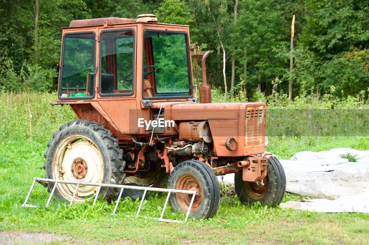 transportation, mode of transportation, land vehicle, land, plant, green color, day, grass, field, nature, tree, agricultural machinery, wheel, no people, agricultural equipment, agriculture, non-urban scene, tractor, machinery, stationary, outdoors, tire