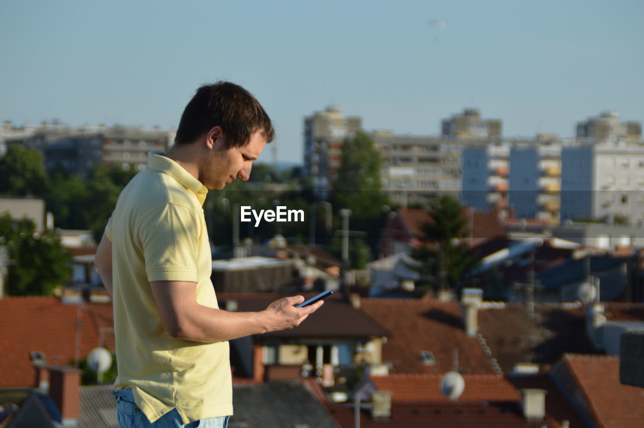 Man using phone by buildings in city against clear sky