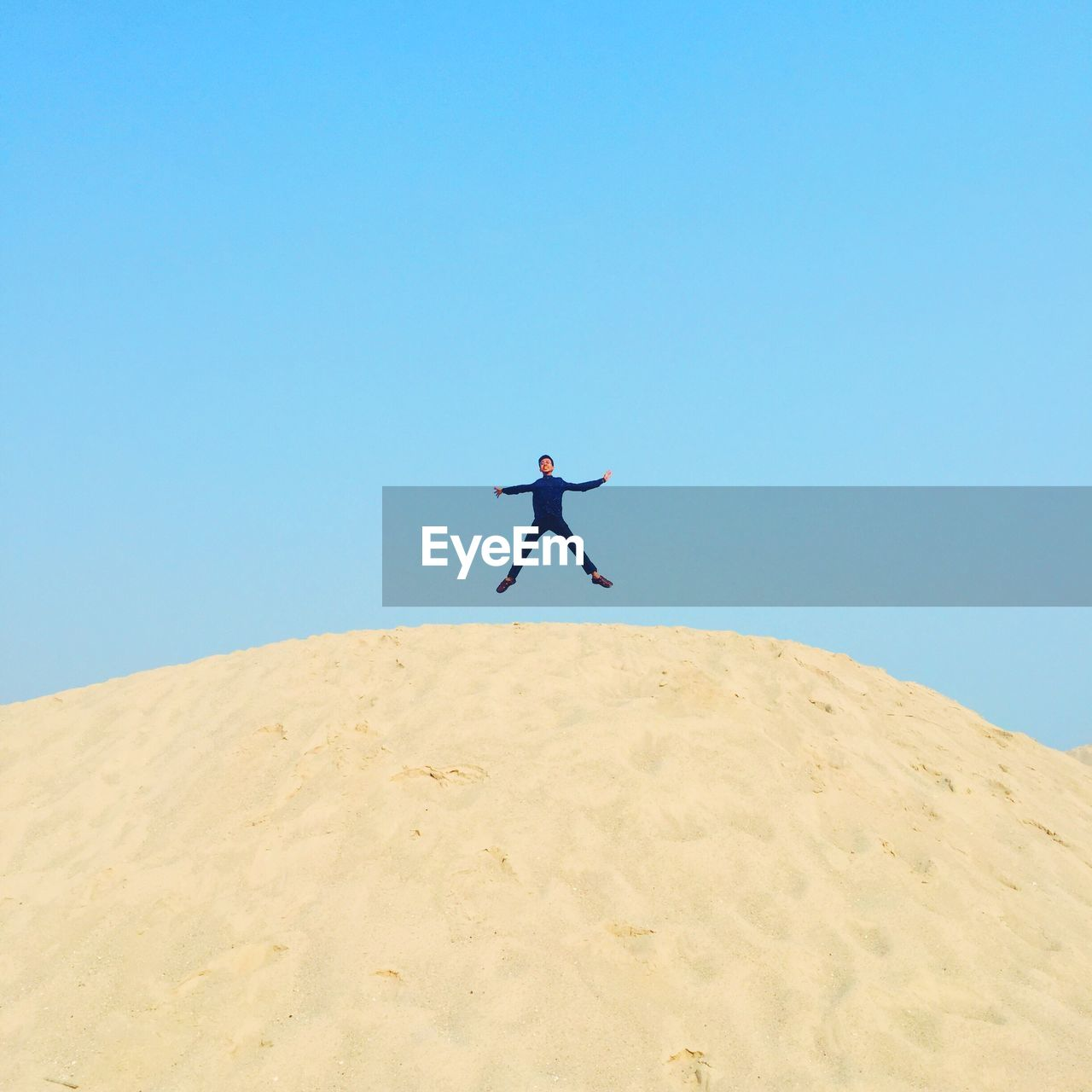 Low angle view of man with arms outstretched jumping over sand at beach against clear blue sky