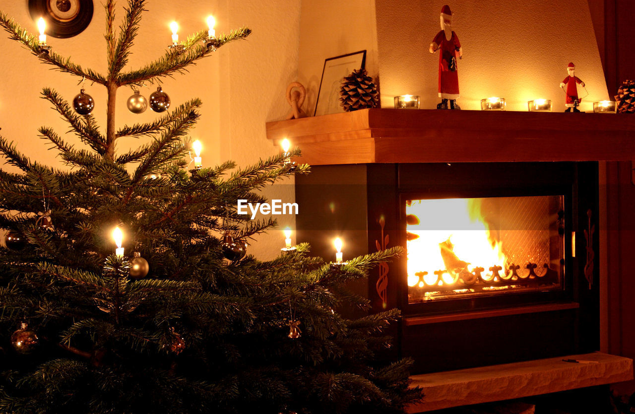 Close-Up Of Illuminated Christmas Tree By Fireplace At Home