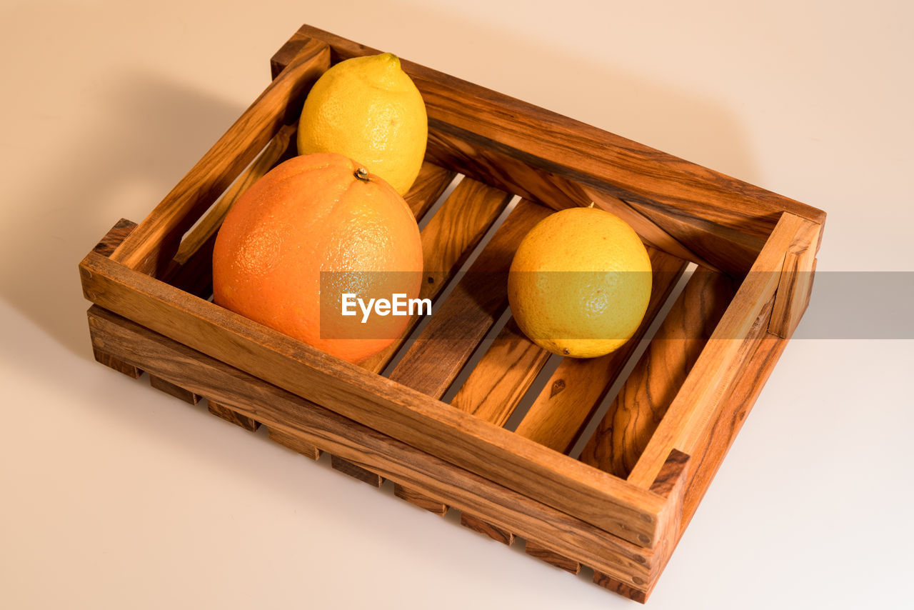 High angle view of citrus fruits in wooden crate over white background