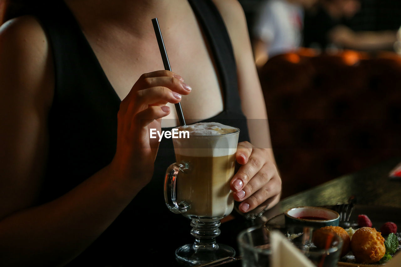 drink, food and drink, refreshment, real people, glass, table, coffee, cafe, restaurant, human hand, women, indoors, drinking glass, focus on foreground, one person, household equipment, business, lifestyles, midsection, adult, hand, hot drink, froth, latte, drinking