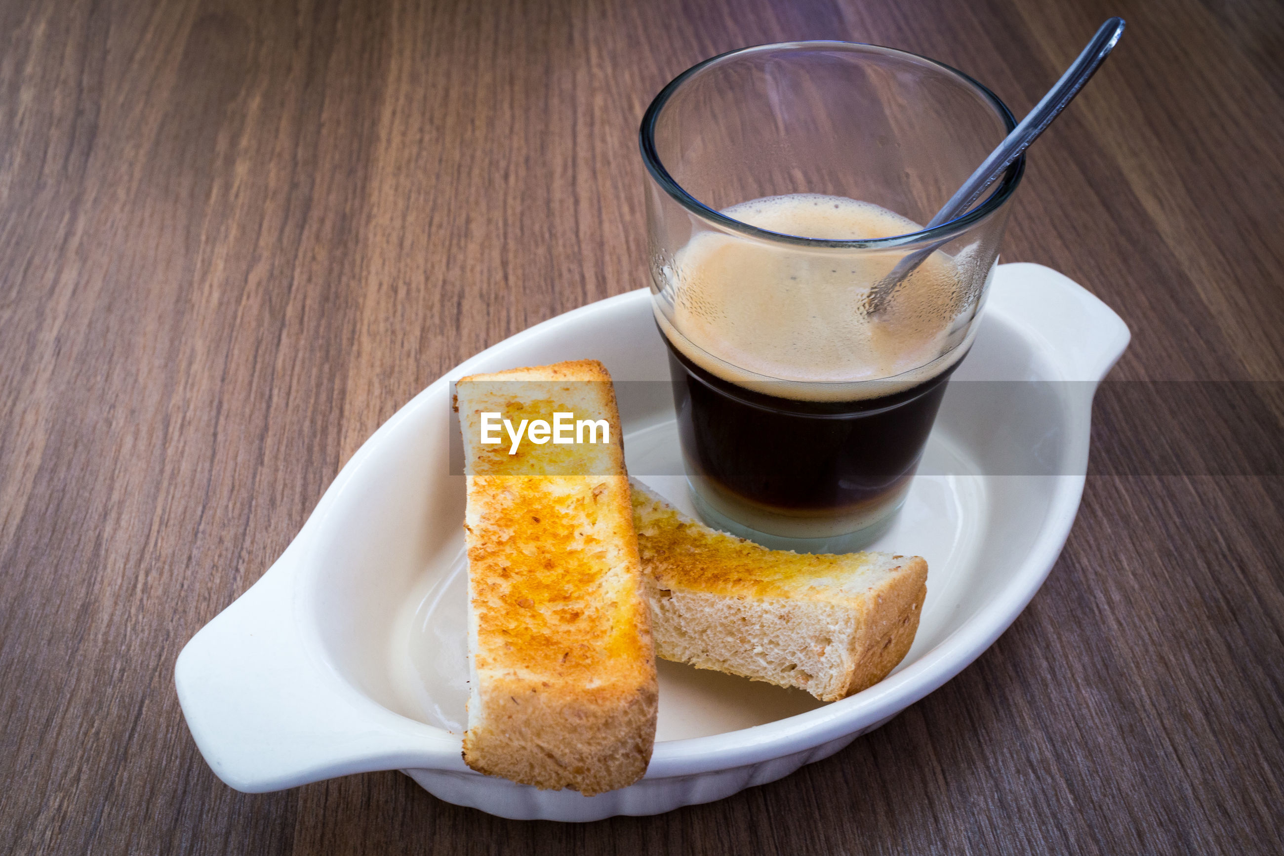 Close-up of bread slices and black coffee in plate on table