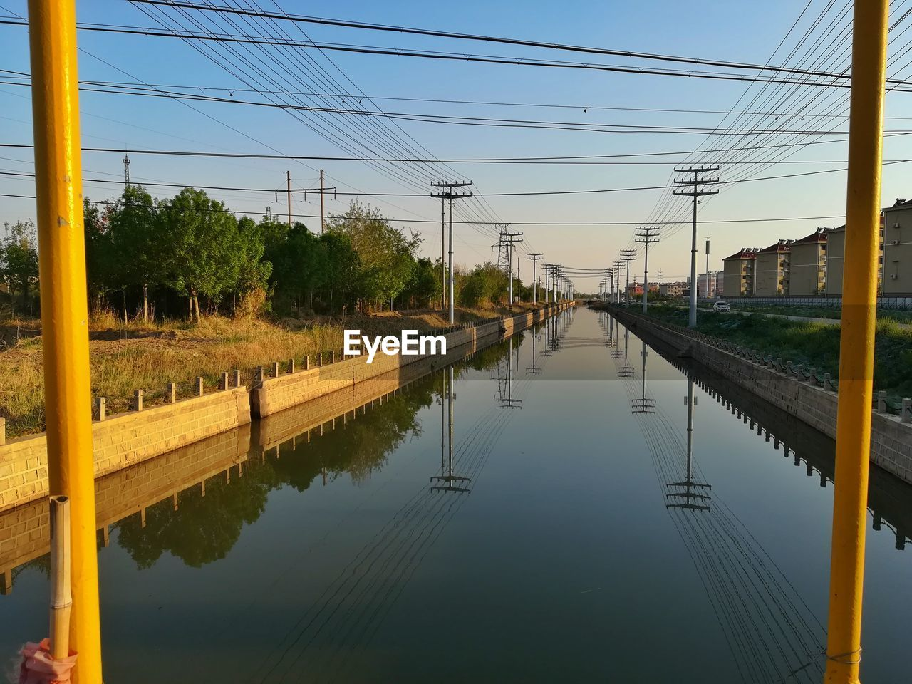 sky, water, reflection, cable, electricity, technology, electricity pylon, connection, nature, power line, no people, plant, fuel and power generation, tree, power supply, diminishing perspective, transportation, architecture, built structure, outdoors, canal, telephone line