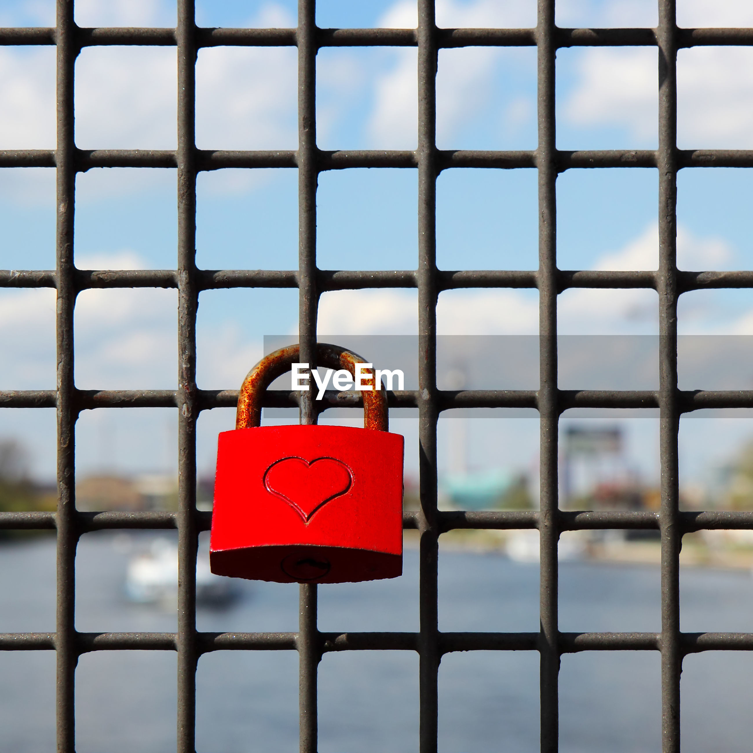 Close-up of love lock on metal grate