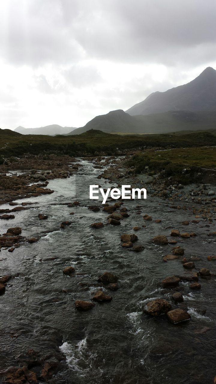 River stream amidst rocks against cloudy sky