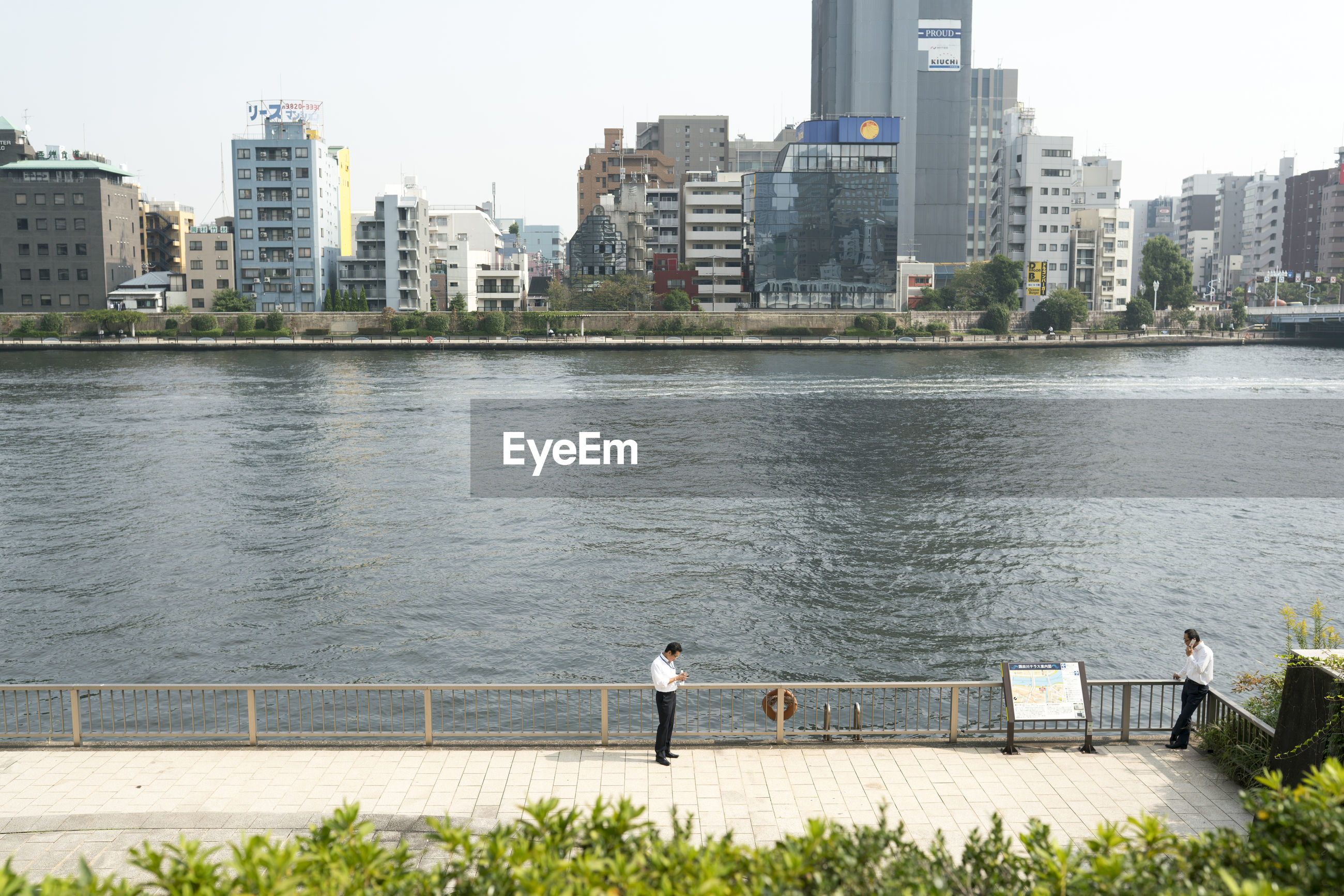 REAR VIEW OF MAN STANDING BY RIVER AGAINST BUILDINGS