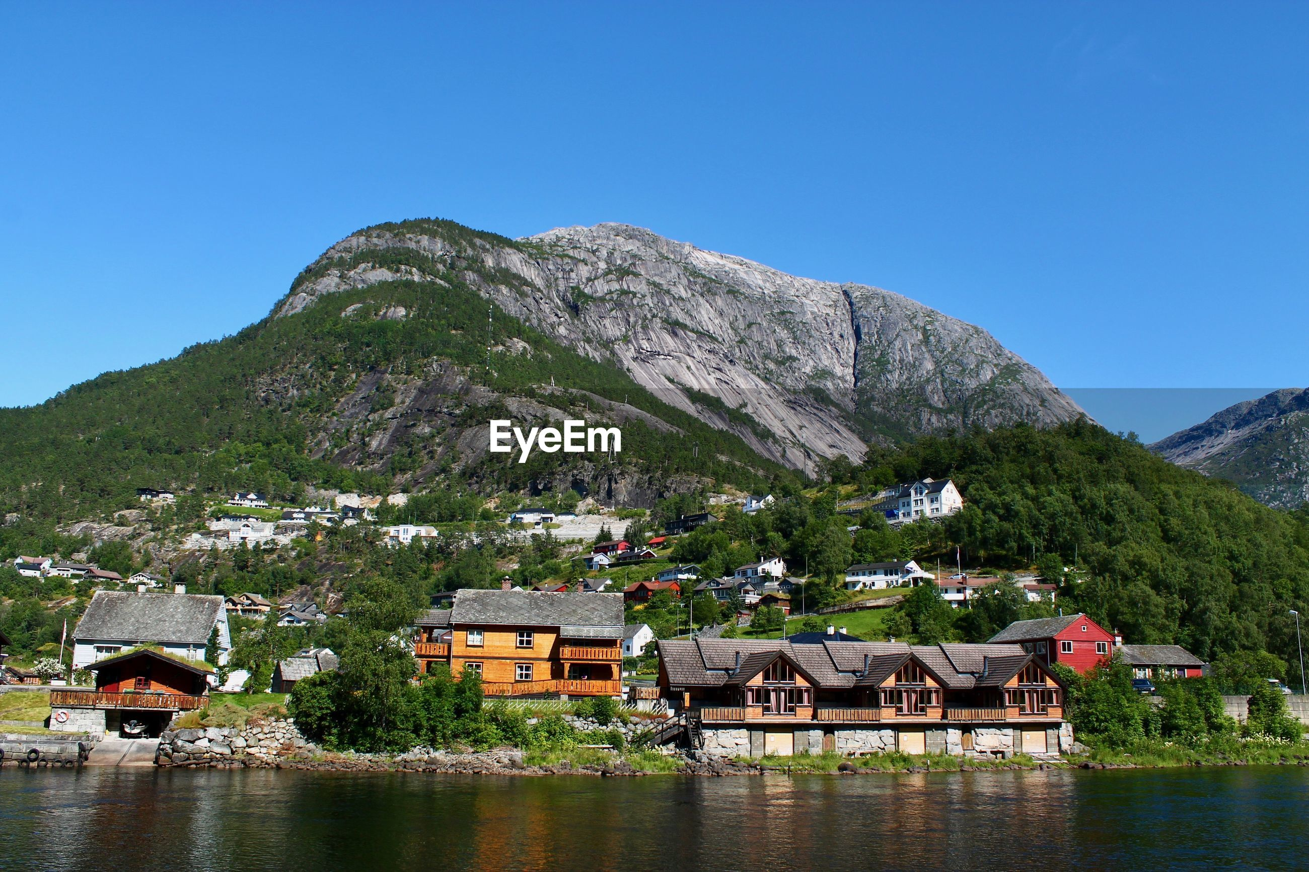 HOUSES IN A LAKE WITH MOUNTAIN IN BACKGROUND