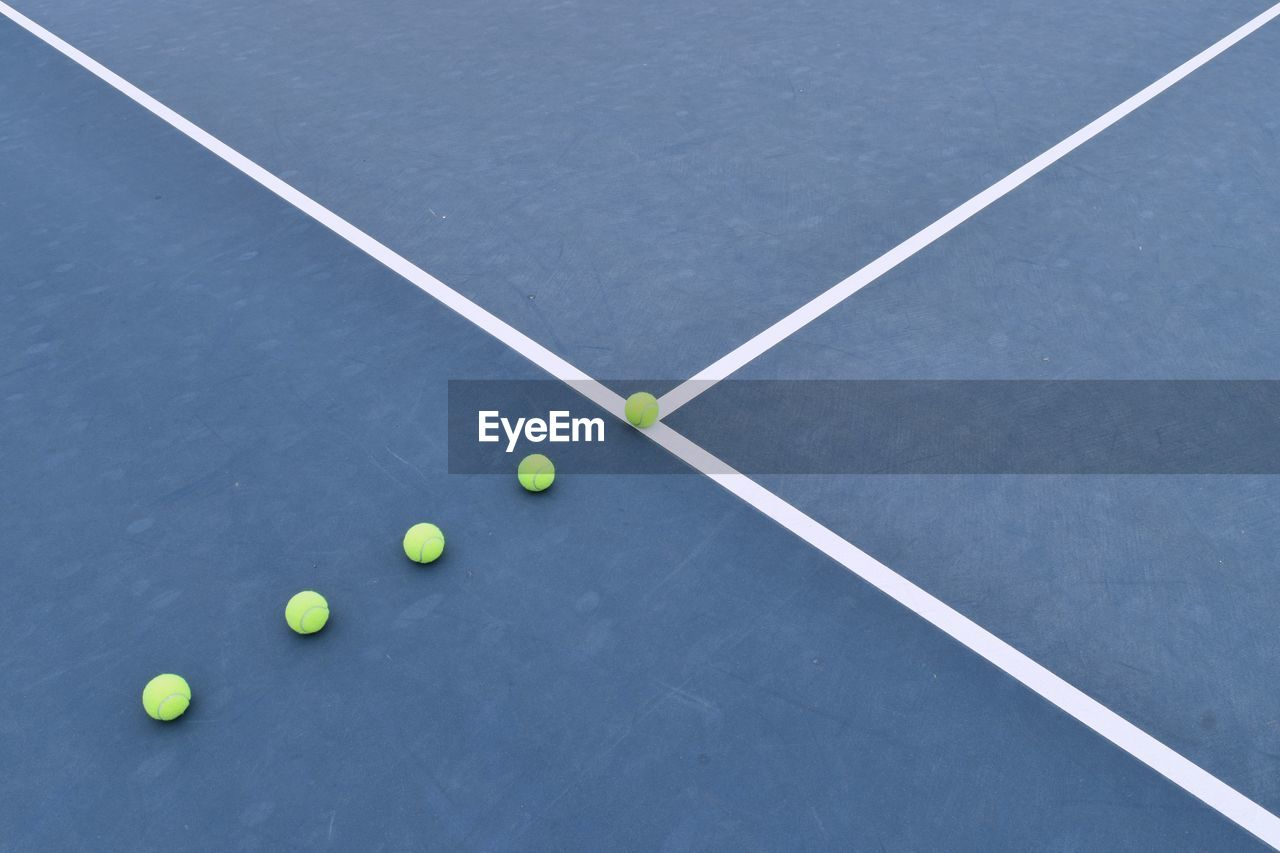 High Angle View Of Balls At Tennis Court